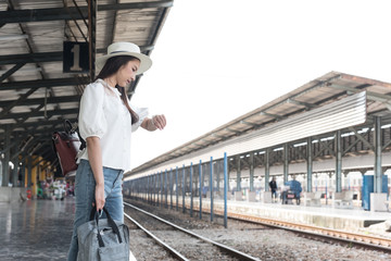 Asian traveler woman wait train at railway station.Travel holiday,relaxation concept.