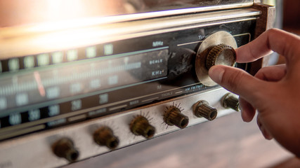Male hand turning retro radio button. Listen to music or news with old classic radio receiver. Vintage lifestyle
