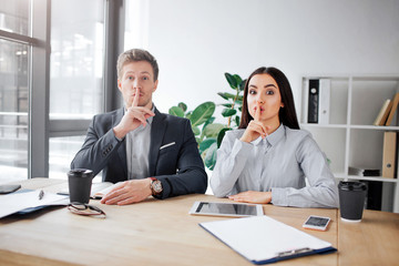 Attentive young man and woman sit at table and look on camera. They are in meeting room. People hold finger on lips. This is hush sign.