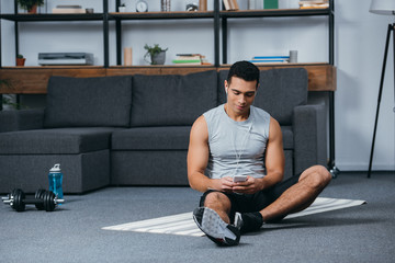 bi-racial man holding smartphone and listening music in earphones on fitness mat