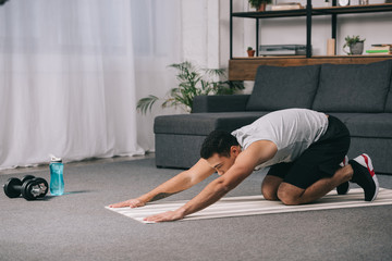bi-racial man doing stretching exercise for back on fitness mat