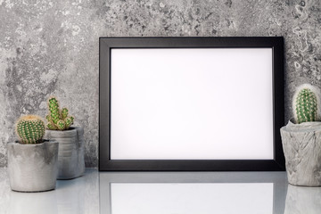 Black empty mockup frame on the background of a stone wall. Cactuses in concrete diy pots. White smooth shelf