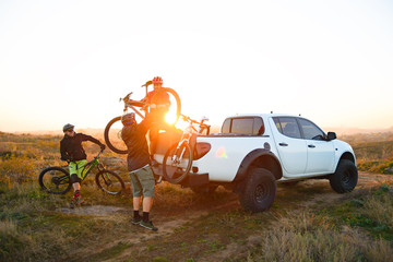 Friends Taking MTB Bikes off the Pickup Offroad Truck in Mountains at Sunset. Adventure and Travel...