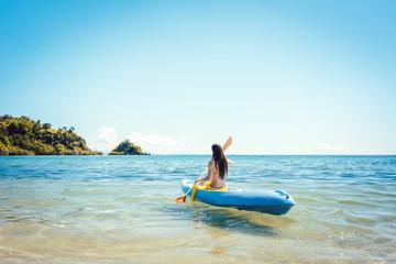 Frau paddelt in ihrem Kajak auf dem Meer im klaren Wasser