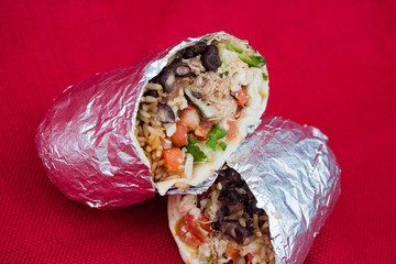 Burrito Wrapped in Aluminum Foil on a red background