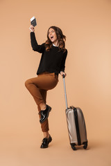 Amazing young woman posing isolated holding passport with tickets and suitcase.