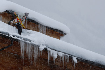 A man shovels snow on a rooftop during heavy snowfall in Flachau
