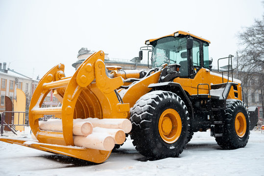 Yellow wheel front end log loader. Forestry equipment for moving wood and other materials. Hydraulic manipulator. Heavy diesel tractor, industrial machinery. Winter time