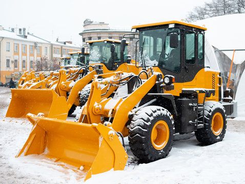 Yellow wheel front loaders. Construction and handling equipment. Heavy diesel tractor, construction machinery, industrial vehicle. Winter time