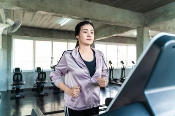 Attractive sport women running on treadmill in industrial loft gym