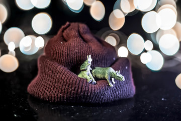 Close up of red colored woolen cap with some toy animals on it on wooden surface with bokeh background of colorful lights.