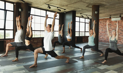 In de dag School de yoga Millennials practising yoga in modern loft studio