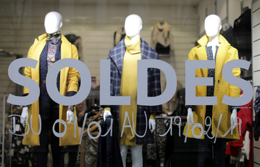 """The word """"Sales"""" is seen on a clothing store's front window on the eve of the start of winter sales in Nice"""