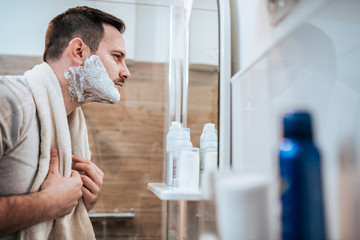 Handsome man looking at mirror with shaving cream on his face.
