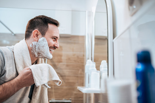 Portrait of a handsome man with shaving cream on his face and towel while standing in the bathroom, looking at mirror.