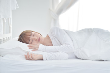 On the bed in the white room.Beautiful woman sleeping in the bedroom.Asian girl sleep well.Sleeping in a white room makes you feel comfortable.Warm tone.