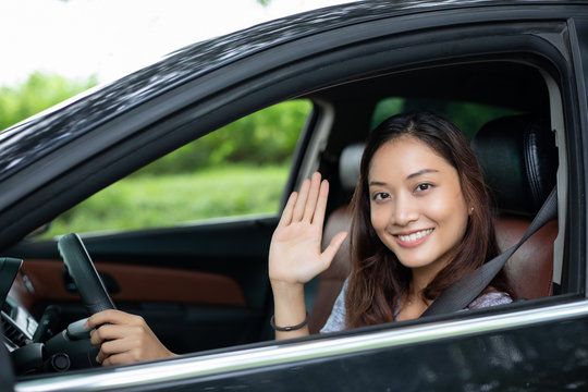 Beautiful Asian woman smiling and enjoying.driving a car on road for travel