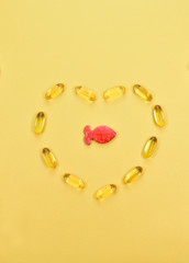 Omega 3. Fish fat, in capsules, on a yellow background.  Healthy Eating. Vitamin D, E, A Fish Oil Capsules. fish oil from the heart.