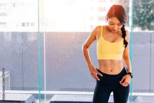 38f98452c3e84 Portrait of young fit Asian woman standing in gym