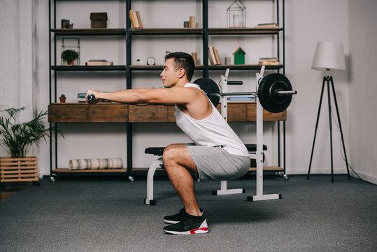 bi-racial man exercising with dumbbells in living room