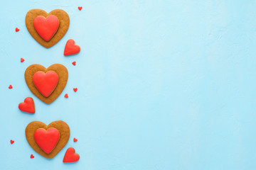 Red heart shaped cookies on pastel blue background.