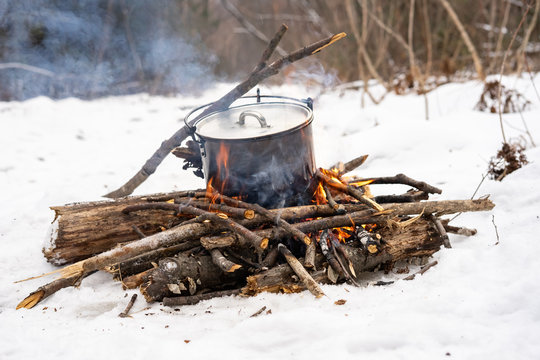 Winter hike: a small bonfire in the forest and a pot on the fire.