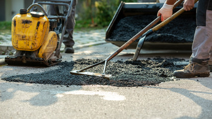 Low angle view of two workers arranging fresh asphalt mix with rakes and shovel Wall mural