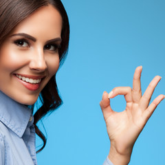 Showing okay gesture businesswoman, on blue