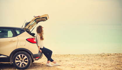 Happy stylish young woman traveler on beach road sitting on white crossover car, holding hat in hand. Banner. Travel, summer vacation, holiday, freedom concept. Digital detox