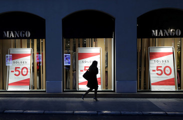 A woman walks past placards announcing a 50% discount displayed on a clothing store's front window on the eve of the start of winter sales in Nice