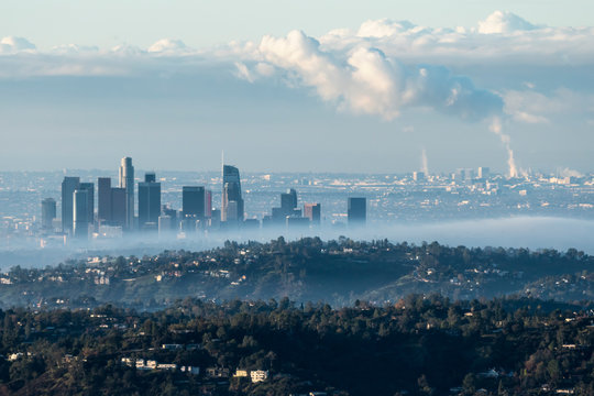 Foggy morning skyline view of downtown Los Angeles with steaming South Bay refineries and industrial facilities in background.  Photo taken from hilltop near Pasadena, California.