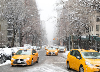 New York City taxis drive down Fifth Avenue through the snow during a winter blizzard in Manhattan