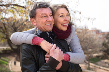 senior man and mature woman together against blured trees of park