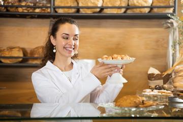 Smiling female enjoy selling tarts
