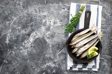Small sea fish smelt or sardine before cooking in a cast-iron form for baking with lemon, butter and salt. Top view. On a dark background.