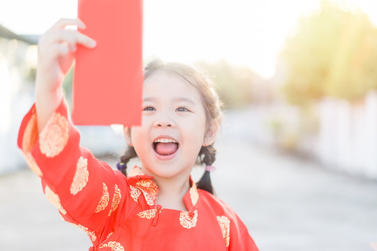 4 years old asian chinese child girl receive money from her mother.Happy Little asian girl in chinese traditional dress smiling and holding red envelope.Happy chinese new year concept.
