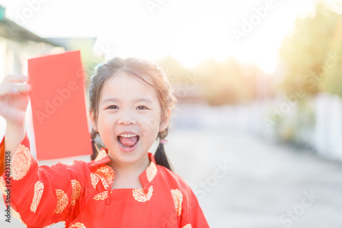 62dd4257ac02 4 years old asian chinese child girl receive money from her mother.Happy Little  asian girl in chinese traditional dress smiling and holding red envelope.