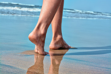 Women's legs go on the sand by the sea.