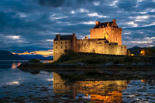 Illuminated Eilean Donan Castle and Loch Alsh at night.