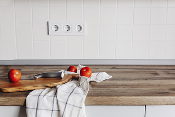 Cooking food on modern kitchen, knife on wooden cutting board with vegetables, spices on wooden tabletop. Home food. Stylish kitchen furniture in grey color in scandinavian style.