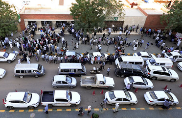 People queue to withdraw money from an automated teller machine (ATM) in Khartoum