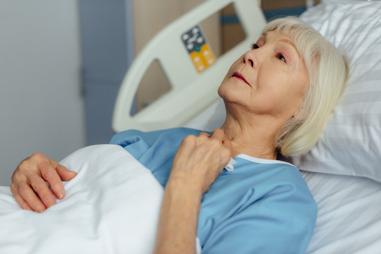 selective focus of lonely senior woman lying in hospital bed and crying