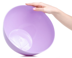 Lilac plastic bowl in hand on a white background. Isolation
