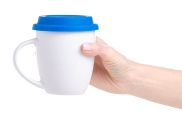 White caup mug with blue lid in hand on white background isolation