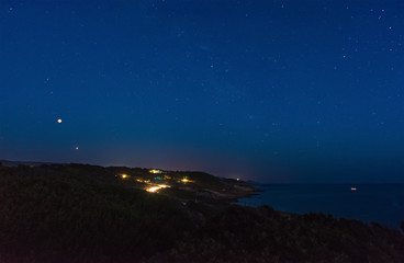 red moon and stars over the coast
