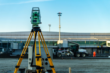 Surveyor equipment (theodolite) on construction site of the airport, building or road with construction machines in background