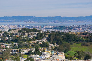 Aerial views of residential areas of San Francisco, San Francisco bay, Oakland and industrial areas in the background, California