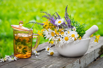 Healthy herbal tea cup, mortar of medicinal herbs on wooden board outdoors.