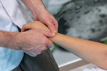 Osteopath therapist makes a lymphatic massage on the wrist.