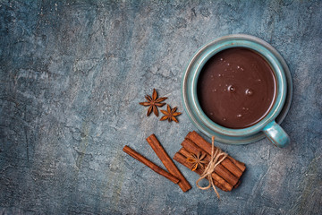 Homemade spicy hot chocolate in ceramic cup with cinnamon stick and anise stars